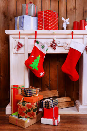 Fireplace with gifts and Christmas decoration on wooden wall background photo