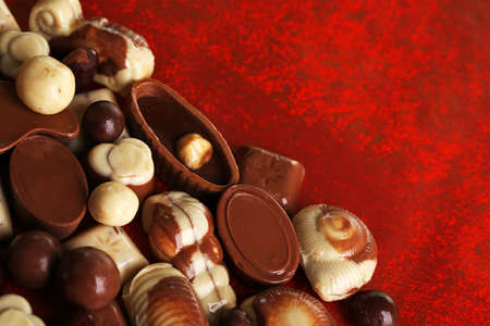 kinds: Different kinds of chocolates on red background