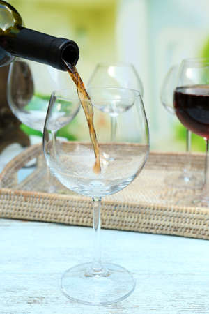 red wine pouring: Red wine pouring into wine glass, close-up