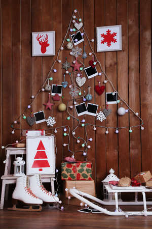 christmas atmosphere: Garland in shape of Christmas tree on wooden wall background, gift boxes and lantern. Christmas atmosphere concept Stock Photo