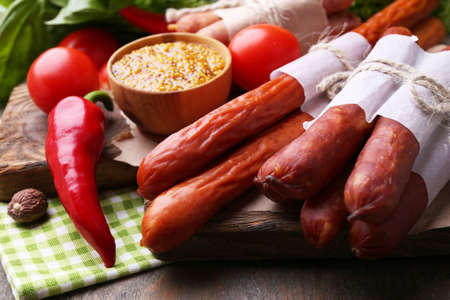 Assortment of thin sausages, mustard in bowl and spices on cutting board, on wooden background photo