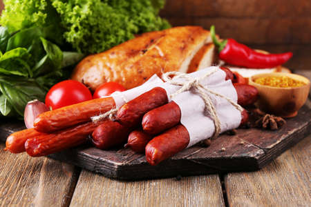 Assortment of thin sausages, bread, mustard in bowl and spices on cutting board, on wooden background photo