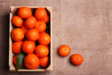 Fresh ripe mandarins in wooden box, on sackcloth background photo