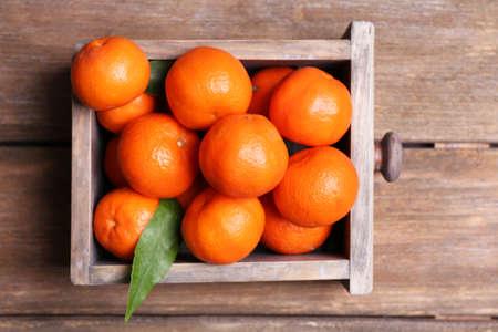 Fresh ripe mandarins in wooden box, on wooden background photo