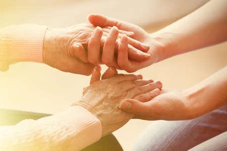 manos entrelazadas: Viejo y joven de la mano sobre fondo claro, de cerca Foto de archivo