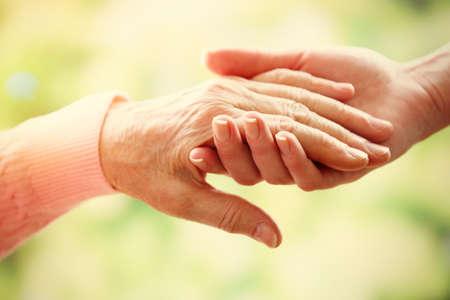 manos sosteniendo: Viejo y joven de la mano sobre fondo claro, de cerca Foto de archivo