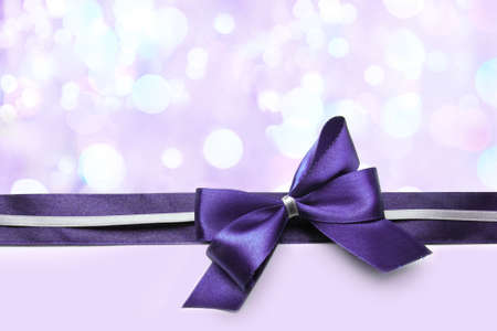 Color satin ribbon bow on bright background photo