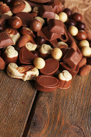 kinds: Different kinds of chocolates on wooden table close-up