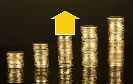Small house standing on stack of coins isolated on black photo