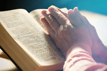 Handen van oude vrouw met een Bijbel op tafel, close-up