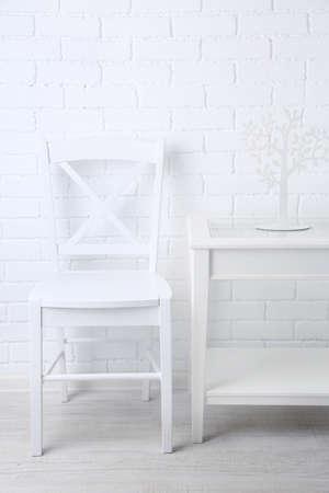 nightstand: Chair and nightstand on white brick wall background Stock Photo