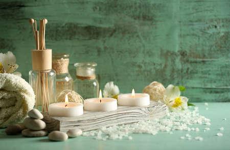 peluqueria y spa: Composici�n de tratamiento de spa, velas en un taz�n con agua en el fondo de madera Foto de archivo