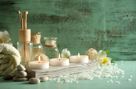 spa therapy: Composition of spa treatment, candles in bowl with water on wooden background Stock Photo