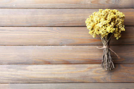 Bouquet of dried flowers on wooden planks background photo