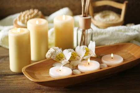 oil massage: Composition of spa treatment, candles in bowl with water on wooden background Stock Photo