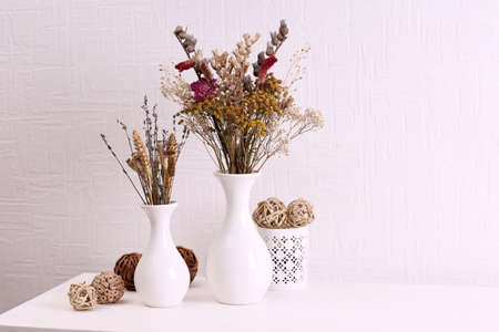Composition of dried flowers on white wall background photo