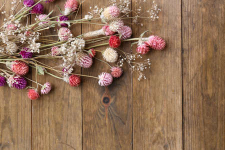 Dried flowers on rustic wooden planks background photo