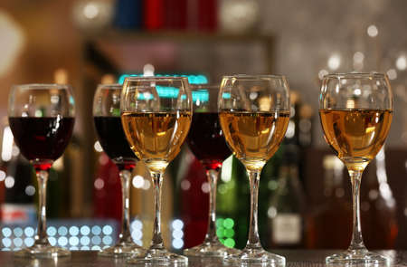 Glasses of wine on counter and bar on background photo