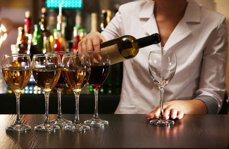 Bartender working at counter on bar background photo