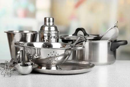 steel pan: Utensilios de cocina de acero inoxidable en la mesa, sobre fondo claro