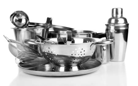 Stainless steel kitchenware on table, isolated on white photo