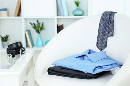 moda ropa: Ropa de hombre en silla con estantes en el fondo Foto de archivo