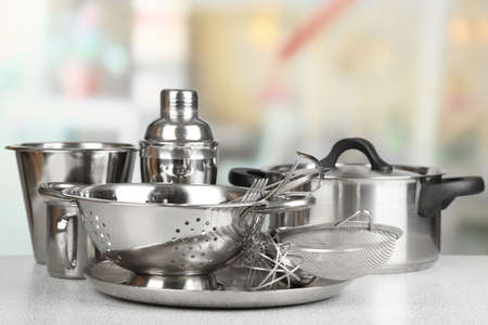Stainless steel kitchenware on table, on light background photo