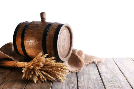 Old barrel with wheat on table on white background photo