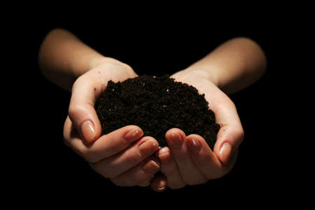 soil conservation: Handful of soil on dark background