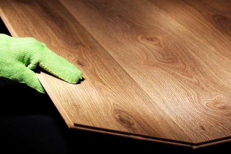 carpenter worker installing laminate flooring photo