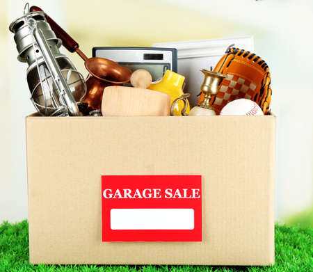 baseball stuff: Box of unwanted stuff ready for a garage sale, on green grass