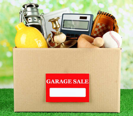 garage: Box of unwanted stuff ready for a garage sale, on green grass