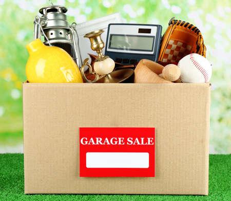 Caja de cosas no deseados listo para una venta de garaje, en la hierba verde Foto de archivo