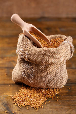 Mustard seeds in bag on  wooden background