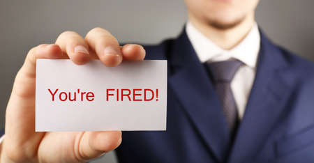 you are fired: Businessman holding card with text You are fired Stock Photo