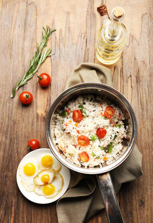 Tasty rice in pan on wooden table photo