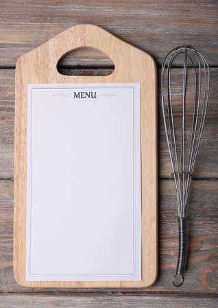 egg whisk: Cutting board with Menu sheet of paper with egg whisk on rustic wooden surface background Stock Photo