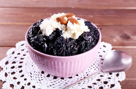Dessert with prunes and almonds in bowl on lace doily and wooden planks background photo
