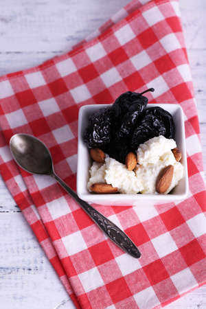 prunes: Dessert with prunes and almonds in bowl on wooden background