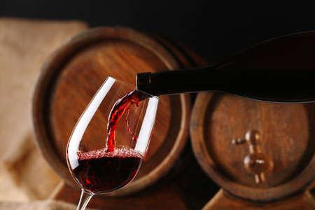 Het gieten van rode wijn uit de fles in glas met houten wijnvaten op de achtergrond Stockfoto