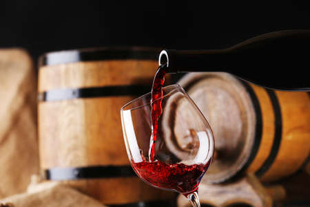 casks: Pouring red wine from bottle into glass with wooden wine casks on background Stock Photo