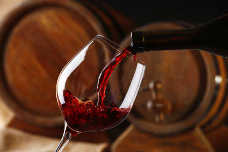 Pouring red wine from bottle into glass with wooden wine casks on background Stockfoto
