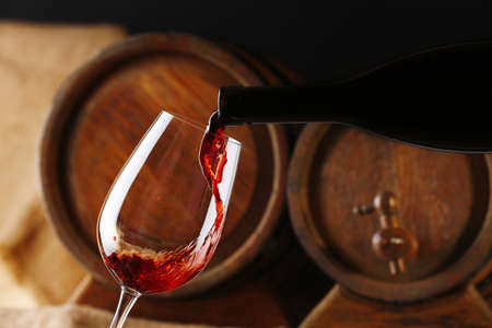 Pouring red wine from bottle into glass with wooden wine casks on background Stock Photo