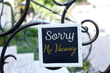 hotel stay: Signboard with text Sorry No Vacancy near hotel Stock Photo