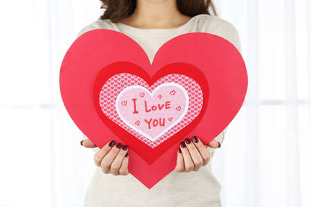 women s health: Girl holding Valentine card on bright background