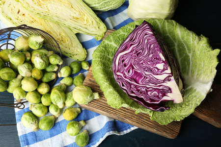the cabbage: assortment cabbages on cutting board on color wooden background