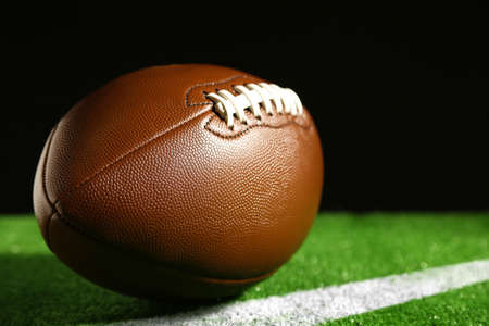 El fútbol americano en la hierba verde, sobre fondo negro