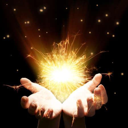 Hands with sparkler light on dark background photo