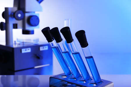 Laboratory glassware with blue liquid on bright background photo