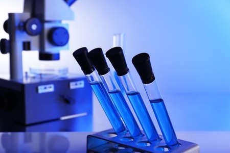 Laboratory glassware with blue liquid on bright background photo